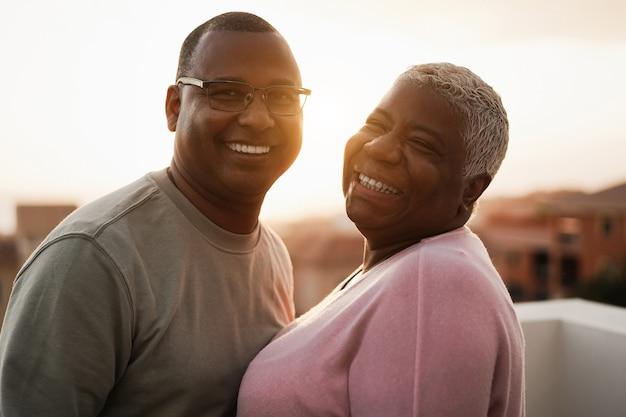 Glückliches schwarzes paar, das zarten moment draußen bei sommersonnenuntergang hat