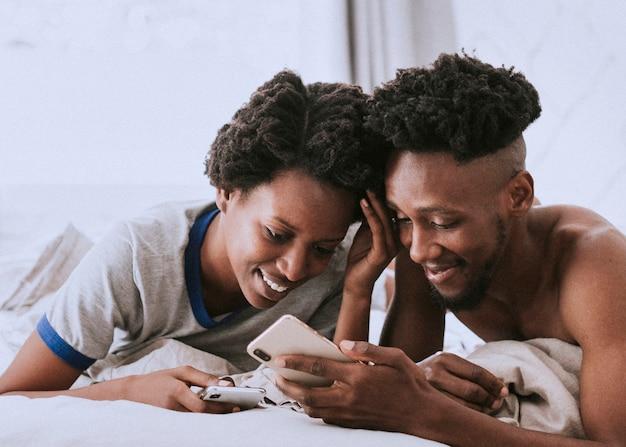 Glückliches schwarzes paar, das zusammen auf einem smartphone spielt