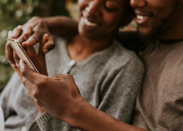 Glückliches schwarzes paar mit einem smartphone