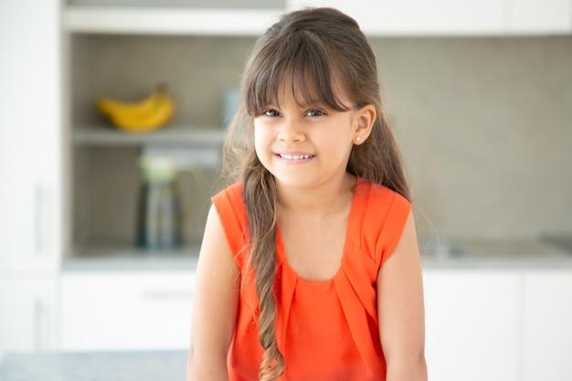 Glückliches schwarzhaariges lateinisches kleines mädchen, das rotes t-shirt trägt und zu hause aufwirft