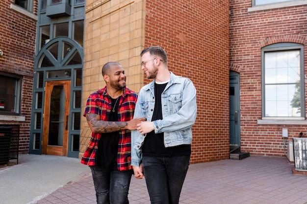 Glückliches schwules paar, das in die stadt geht, lebensstil stockbild