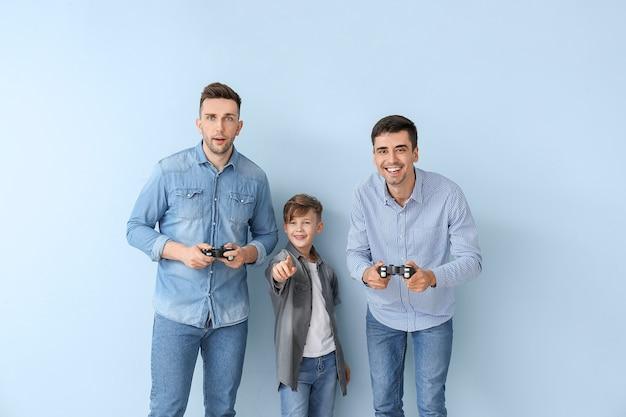 Glückliches schwules paar mit adoptiertem kind, das videospiel auf farbigem hintergrund spielt