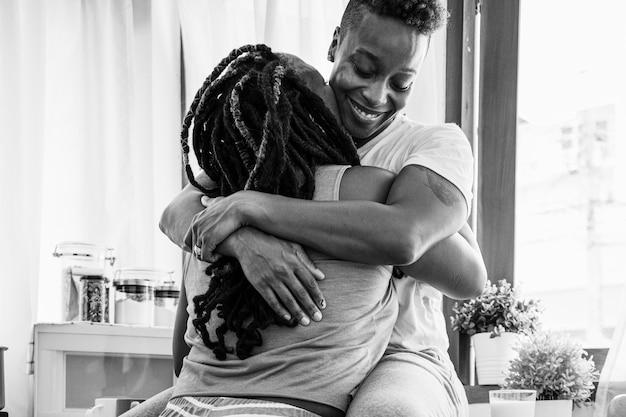 Glückliches schwules paar umarmt sich in der küche