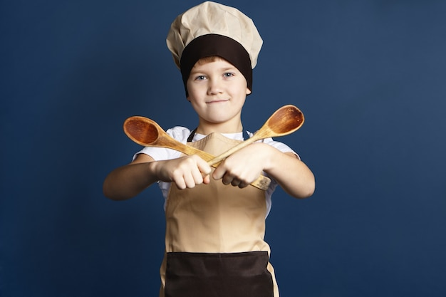 Glückliches selbstbewusstes 10-jähriges männliches kind in kopfbedeckung und schürze des küchenchefs, das zwei holzlöffel vor sich hält, stolz, während es erlaubt ist, mutter zu helfen, abendessen zu kochen, kamera mit lächeln schauend