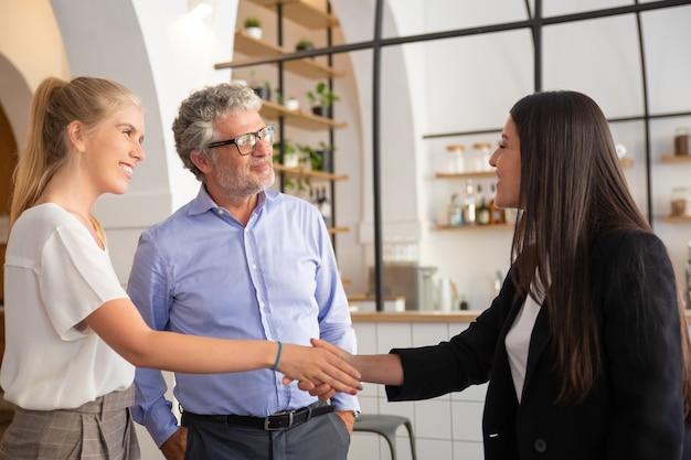 Glückliches, selbstbewusstes weibliches manager-treffen mit kunden und händeschütteln
