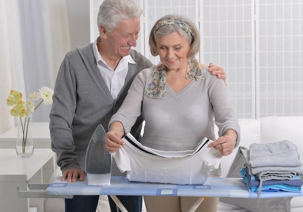 Glückliches seniorenpaar beim bügeln zu hause