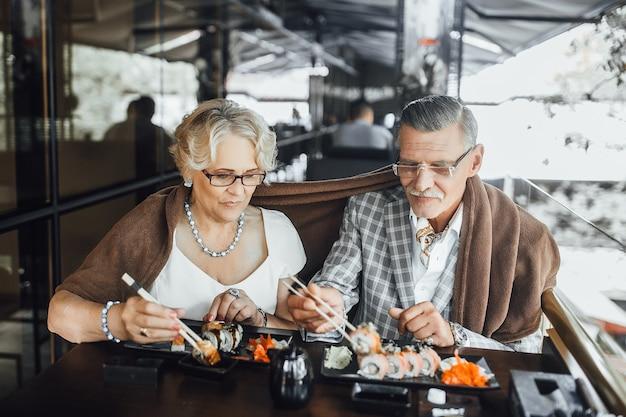 Glückliches seniorenpaar, das ein sushi in einem restaurant genießt und zeit zusammen genießt