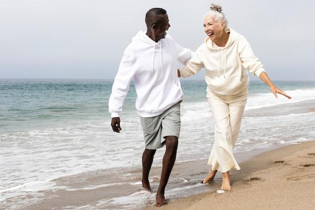 Glückliches seniorenpaar, das sich im winter am strand entspannt