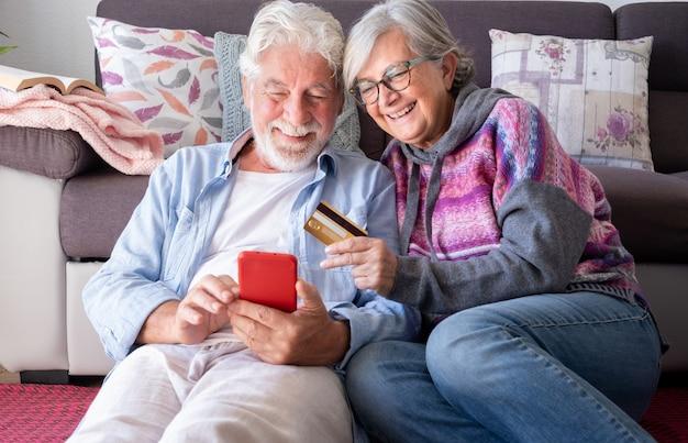 Glückliches seniorenpaar im wohnzimmer zu hause, das spaß beim online-shopping mit kreditkarte, e-commerce, käufer, konsumkonzept hat