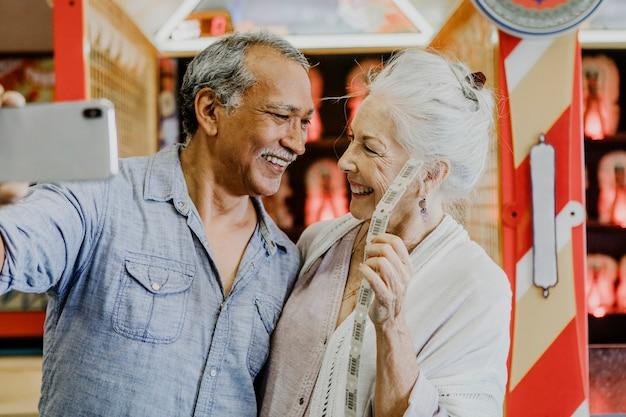 Glückliches seniorenpaar macht ein selfie mit tombola-tickets