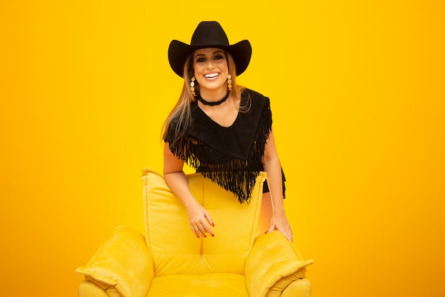 Glückliches sexy cowgirl auf gelbem hintergrund