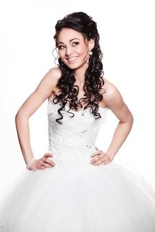 Glückliches sexy schönes brautbrünettmädchen im weißen hochzeitskleid mit frisur und hellem make-up auf weißem hintergrund
