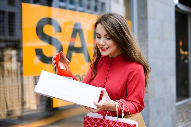 Glückliches shopaholic mädchen mit taschen, die lächeln und neues paar rote hochhackige schuhe halten