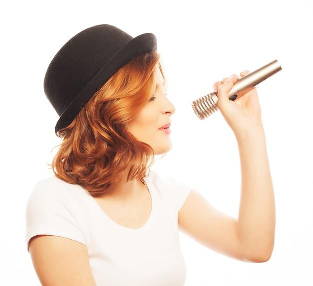 Glückliches singendes mädchen. schönheitsfrau, die weißes t-shirt und schwarzen hut mit mikrofon über weißem hintergrund trägt. hipster-stil.