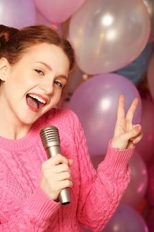 Glückliches singendes mädchen. schönheitshaarhaarfrau mit mikrofon über hintergrund von luftballons.