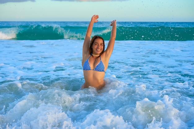 Glückliches sitzen des lateinischen bikinimädchens in karibischen meeren