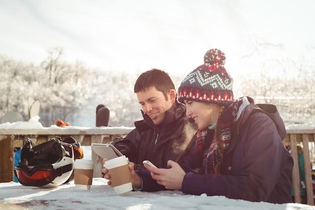 Glückliches skifahrerpaar, das am tisch sitzt, während handy und digitales tablet verwendet werden