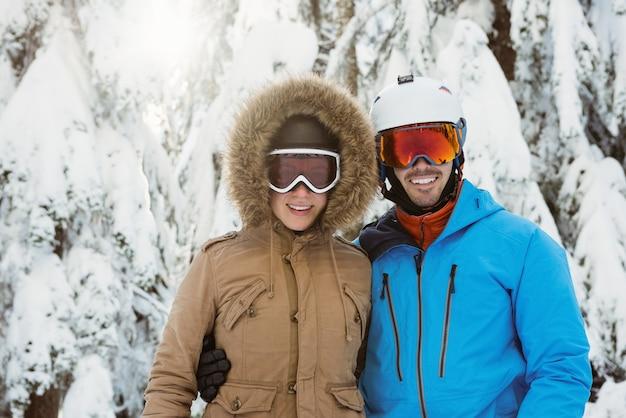 Glückliches skifahrerpaar, das auf verschneite landschaft steht