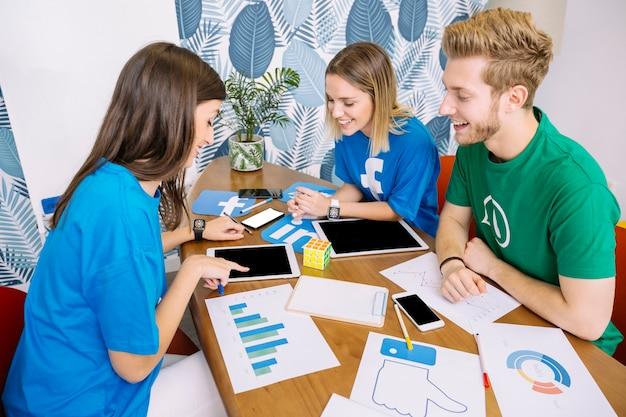 Glückliches social media-team, das digitale tablette betrachtet