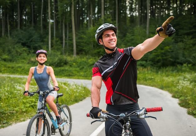 Glückliches sorgloses paarreiten auf fahrrädern an der straße.