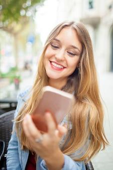 Glückliches sorgloses studentenmädchen, das auf smartphone smsing ist