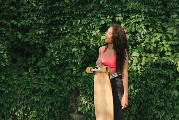 Glückliches spanisches mädchen in der stilvollen straßenkleidung steht mit einem skateboard in der hand