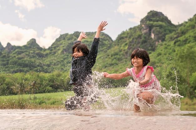 Glückliches spielen mit zwei mädchen im fluss. kinder, die spaß draußen auf sommerlebensstil haben