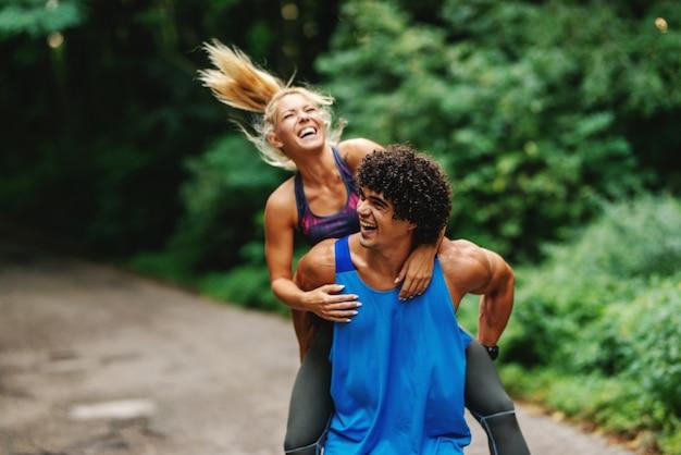 Glückliches sportliches kaukasisches paar, das im sommer huckepack in der natur hat.