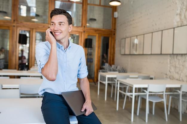 Glückliches sprechen am telefon junger attraktiver lächelnder mann, der im zusammenarbeitenden offenen büro sitzt,