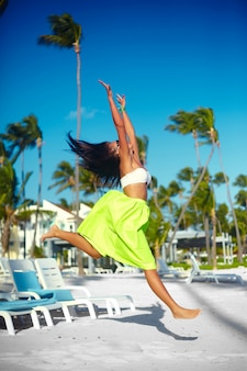 Glückliches städtisches modernes junges stilvolles frauenfrauenmodell im hellen modernen stoff im grünen bunten rock draußen im sommerstrand, der hinter blauen himmel springt