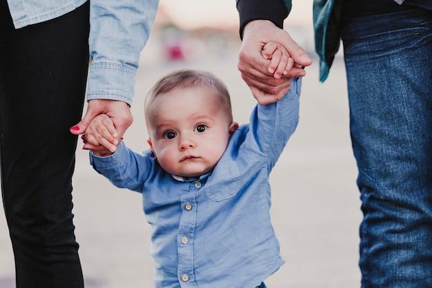 Glückliches stilvolles elternhändchenhalten mit baby und gehen durch die straße, zarter familienmoment.