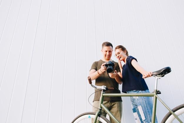 Glückliches stilvolles junges paar, mann und frau, die mit fahrrad stehen, sieht aufregend aus, während fotos in der kamera nach dem fotoshooting im freien betrachtet werden.