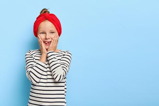 Glückliches stilvolles kleines mädchen mit dem roten stirnband, das aufwirft