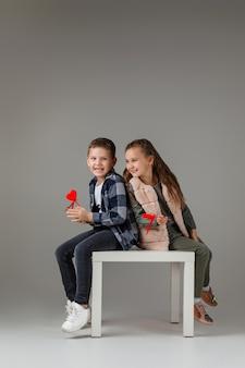 Glückliches stilvolles kleines paarkindmädchen und -junge mit roten herzen auf stock in modischer kleidung, die zusammen sitzen