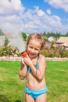 Glückliches strömendes wasser des kleinen mädchens von einem schlauch und von einem lachen