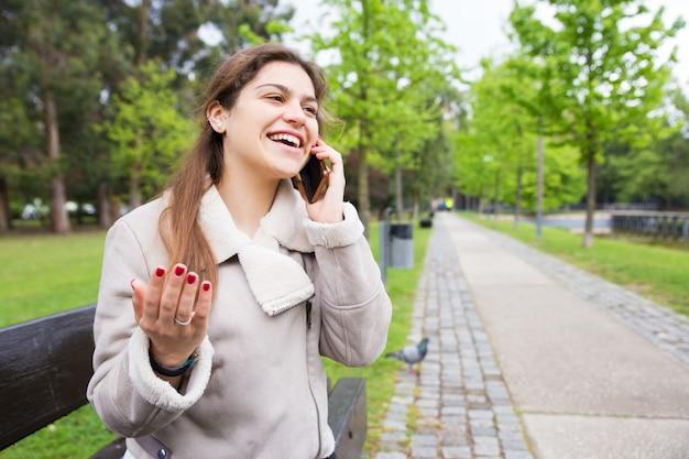 Glückliches studentenmädchen aufgeregt mit lustigem telefongespräch