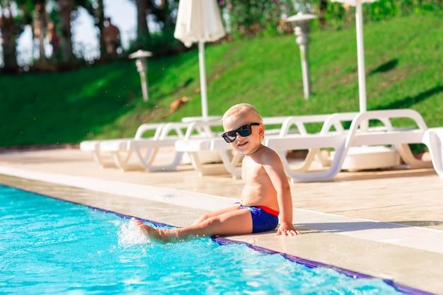 Glückliches süßes baby, das spaß am pool im ferienort hat
