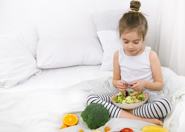 Glückliches süßes kind spielt mit obst und gemüse auf dem bett.