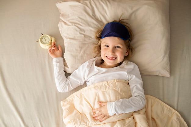 Glückliches süßes kindermädchen liegt lächelnd im bett und hält einen wecker in der hand. freude und guten morgen.