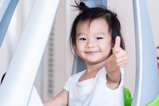 Glückliches süßes kleines asiatisches mädchenreiten auf kleinem auto mit dem daumen oben lokalisiert auf weiß