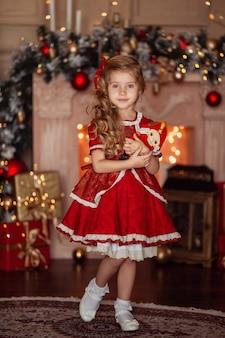 Glückliches süßes kleines blondes mädchen mit langen haaren in einem roten kleid, das auf weihnachten wartet
