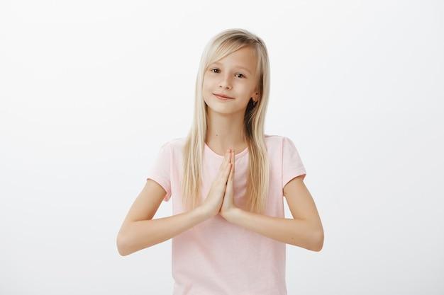 Glückliches süßes kleines kind, blonde frau, die sich mit zusammengeklappten händen bedankt, namaste geste