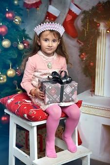 Glückliches süßes kleines mädchen, das auf einem stuhl nahe dem weihnachtsbaum am kamin sitzt, erhielt ein großes schönes geschenk.