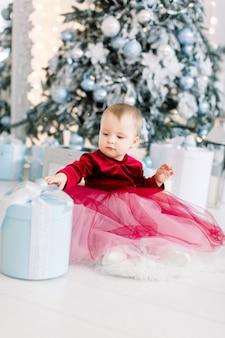 Glückliches süßes kleines mädchen im roten eleganten kleid, das auf dem mehl sitzt und eine geschenkbox öffnet