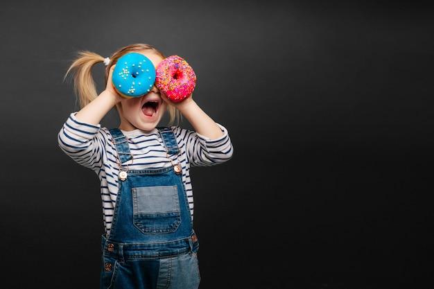 Glückliches süßes mädchen hat spaß, der mit donuts auf schwarzer hintergrundwand gespielt wird. helles foto eines kindes. farbige donuts