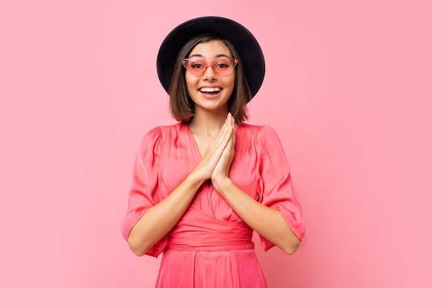 Glückliches süßes mädchen im rosa kleid posiert
