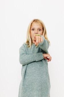 Glückliches süßes mädchen in einem pullover verzieht das kinderlebensstilkonzept