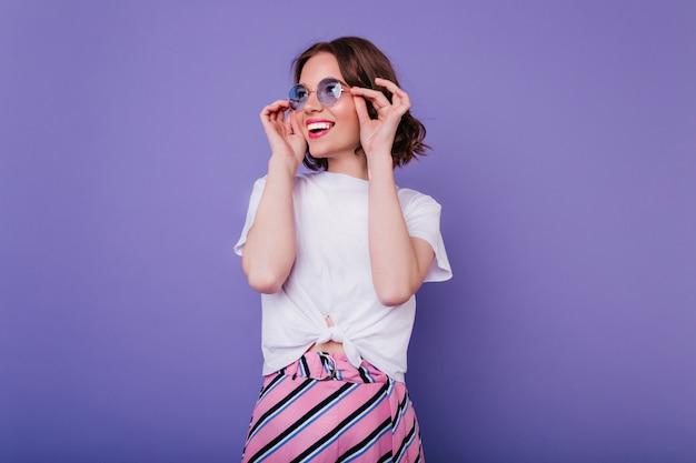Glückliches süßes mädchen mit gewellter frisur, die ihre brille mit lächeln berührt. innenaufnahme der prächtigen lockigen dame im weißen t-shirt, das auf lila wand aufwirft.