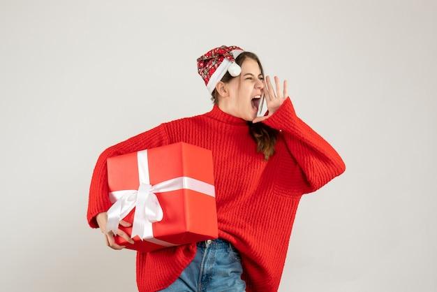 Glückliches süßes mädchen mit weihnachtsmütze, die geschenk hält und schreit, das auf weiß steht