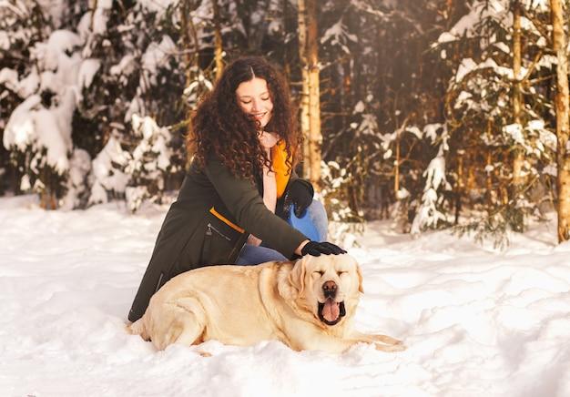 Glückliches süßes mädchen streichelt weißen hund labrodor im winter in der natur